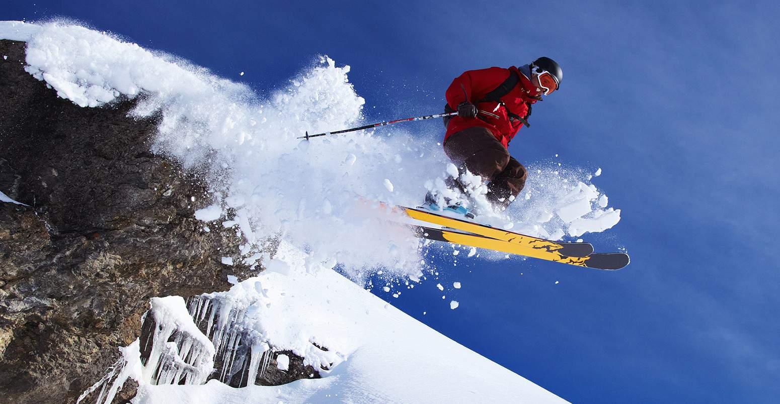 skier going off a cliff with powder