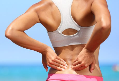 Woman with low back pain holding her back