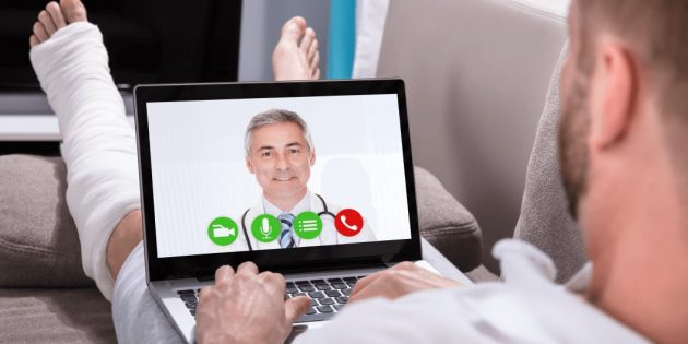 Patient doing telehealth with his doctor with a cast on his foot