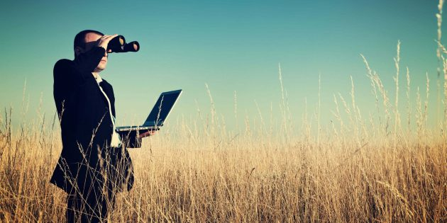 Man looking into a grassy field with binoculars