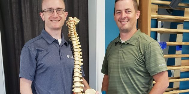 Korey Derocher and David Butler from Align Therapy with a spine and scoliosis stall bars