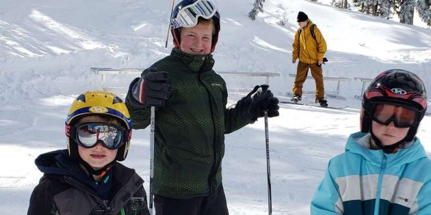 Three kids skiing with helmets on